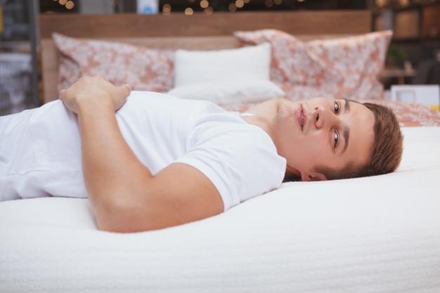 attractive-man-lookin-camera-lying-his-bed_130388-1601
